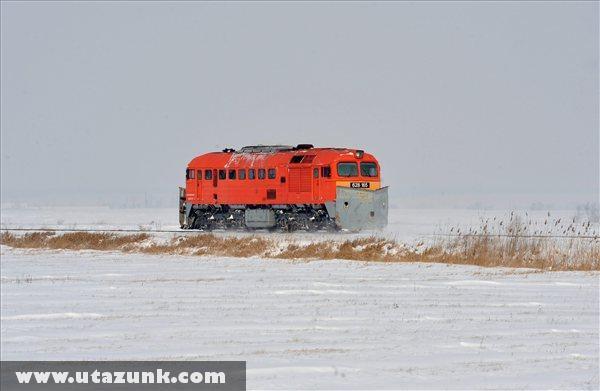 Hóekével fölszerelt M62-es mozdony halad Sárkeresztúr közelében, ahol a Székesfehérvár-Sárbogárd vasútvonalon